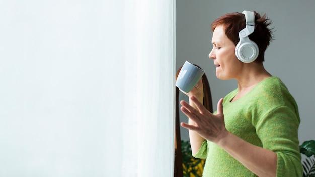 Vista lateral mulher ouvindo música