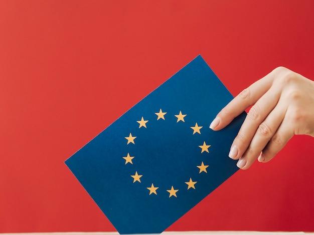 Vista lateral, mulher, pôr, um, europeu, votando, cartão, em, um, caixa