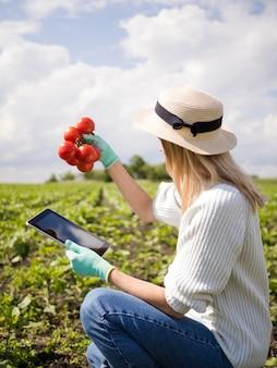 Vista lateral mulher segurando alguns tomates