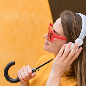 Vista lateral mulher segurando um guarda-chuva enquanto estiver usando fones de ouvido