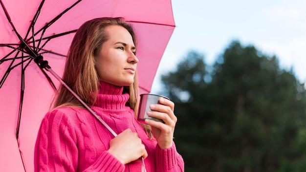 Vista lateral mulher segurando um guarda-chuva rosa