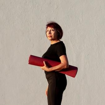 Vista lateral mulher segurando um tapete de fitness