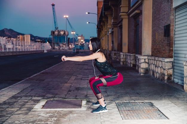 Vista lateral, mulher, squatting, ligado, rua