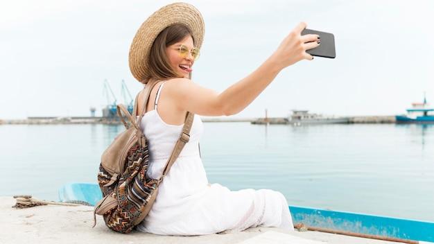 Vista lateral mulher tomando selfie