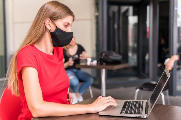 Vista lateral mulher trabalhando e vestindo máscara facial