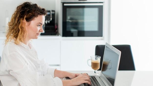 Vista lateral mulher trabalhando no laptop