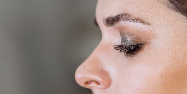 Vista lateral mulher usando maquiagem