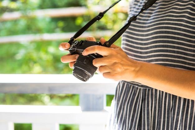 Vista lateral mulher verificando fotos na câmera