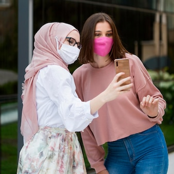 Vista lateral mulheres tomando selfie