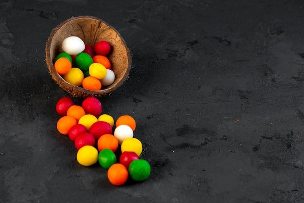 Vista lateral multi coloridas doces em uma casca de coco