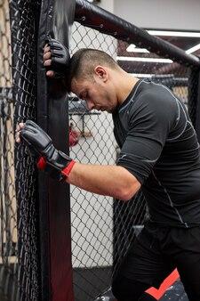 Vista lateral na aptidão desportiva homem cansado passar o tempo no ginásio praticando boxe, descansar, fazer uma pausa. conceito de motivação para esportes de treinamento