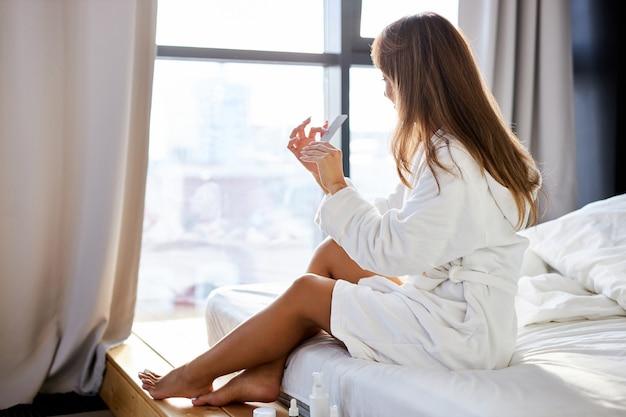 Vista lateral na jovem fêmea em roupão de banho, lixando as unhas no quarto luminoso, nos fins de semana. mulher após banho em casa por causa da epidemia de coronavírus. vida em casa
