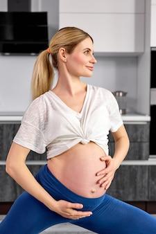 Vista lateral na mulher grávida sorridente, em pé, acariciando a barriga