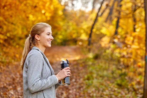 Vista lateral na mulher loira sorridente bebendo água doce na natureza, faça uma pausa durante a corrida, a corrida. sorriso
