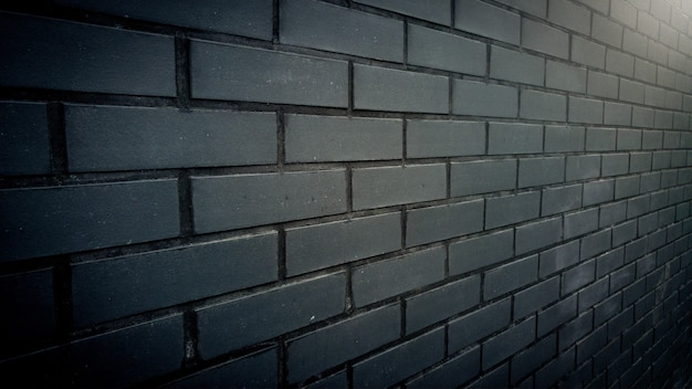 Vista lateral na parede de tijolos pretos iluminada por um poste de luz