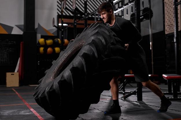 Vista lateral no trabalho ativo do homem - lançando o pneu no treinamento crossfit, homem usando equipamento esportivo. cross fit e treino. atleta forte e bonito.