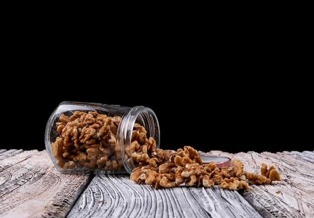 Vista lateral nozes em frascos na mesa de madeira horizontal