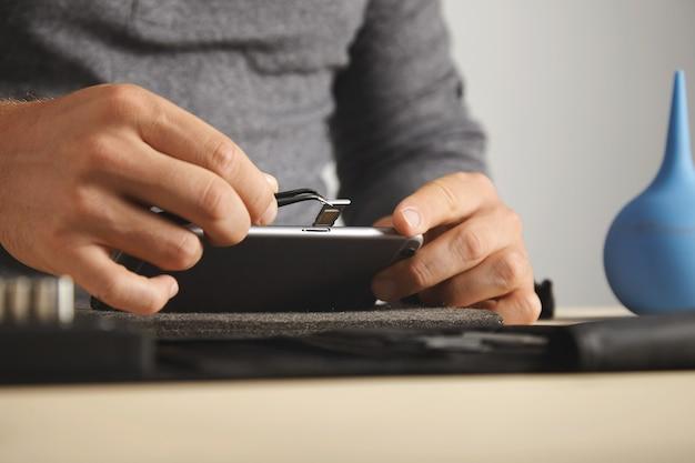 Vista lateral, o mestre usa a ferramenta pincher para remover o slot do cartão sim do smartphone enquanto o desmonta
