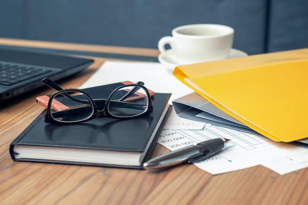 Vista lateral óculos, smartphone, laptop, caderno e caneta em cima da mesa de madeira.