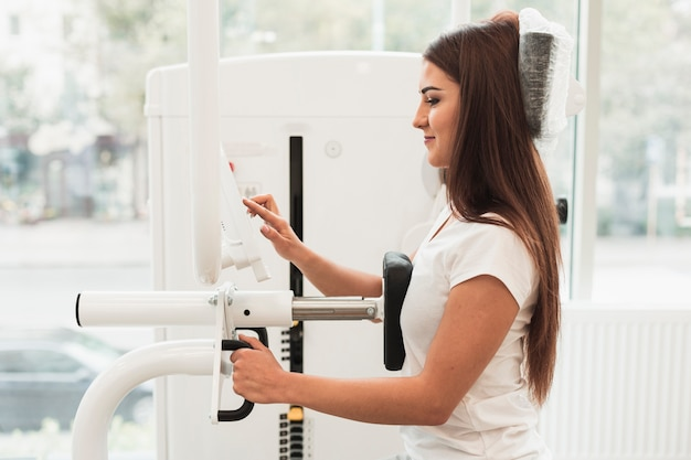 Vista lateral paciente usando máquina de treino médico