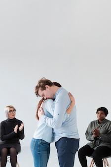 Vista lateral pacientes de reabilitação abraçando
