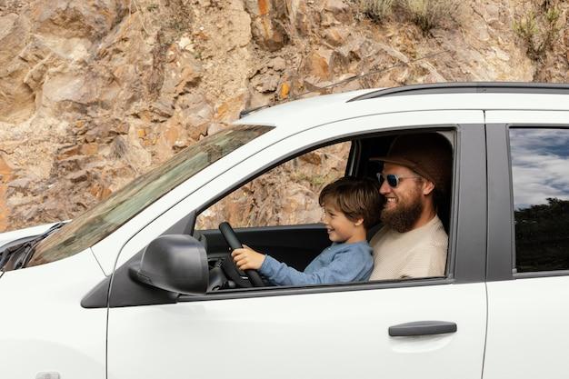 Vista lateral pai com filho no colo dirigindo