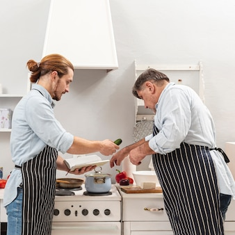 Vista lateral pai e filho cozinhando juntos