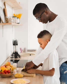 Vista lateral pai ensinando filho a cortar frutas