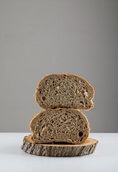 Vista lateral pão cortado na madeira na superfície branca. espaço vertical para texto