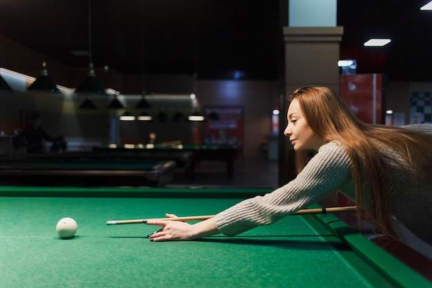 Vista lateral para a menina joga bilhar em um pub escuro