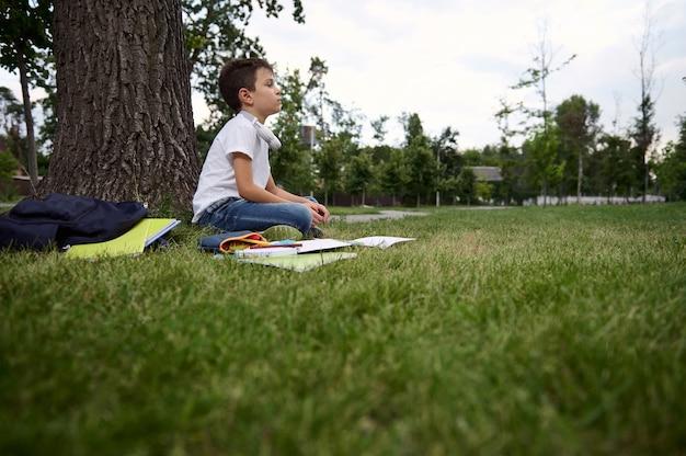 Vista lateral para um menino de escola adorável inteligente e sereno se sente exausto e cansado depois da escola e do dever de casa, senta-se em posição de lótus e medita. livros de exercícios e material escolar na grama