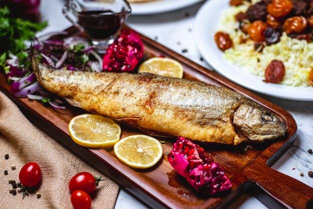 Vista lateral peixe grelhado com cebola roxa de romã e limão em uma bandeja