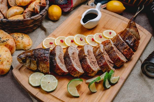 Vista lateral peixe recheado com limão molho de romã limão e pão em cima da mesa