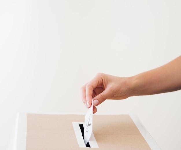 Vista lateral pessoa colocando cédula na caixa