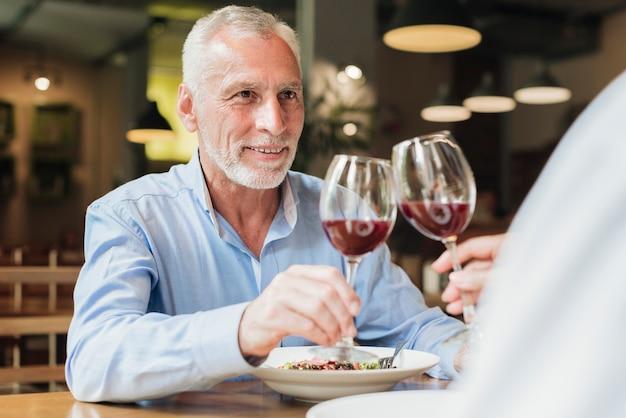 Vista lateral, pessoas, clinking, óculos, em, restaurante