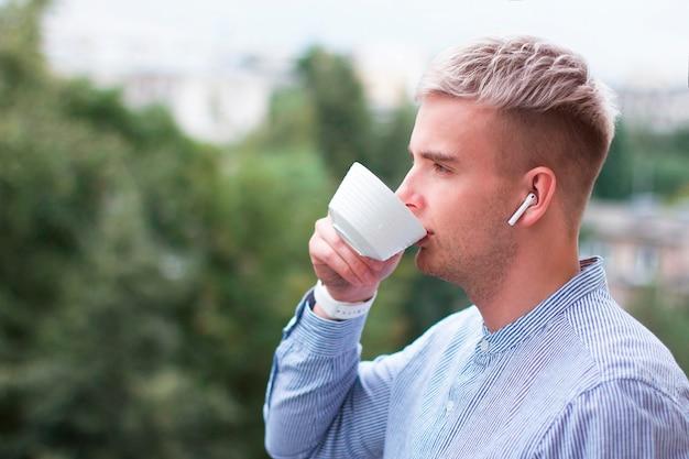 Vista lateral portret de pensativo loiro loiro na camisa, fones de ouvido com uma xícara de café ou chá. jovem com cabelos grisalhos tingidos, ouvindo música em fones de ouvido sem fio, bebendo bebida ao ar livre.