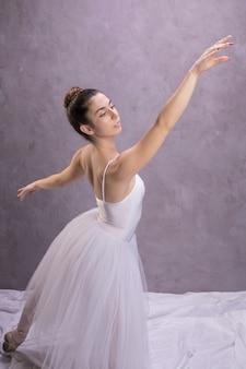 Vista lateral, postura de bailarina com fundo de estuque