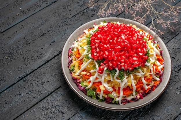 Vista lateral prato de natal prato de natal de batata cenoura beterraba maionese sementes de romã ao lado dos galhos da árvore na mesa cinza