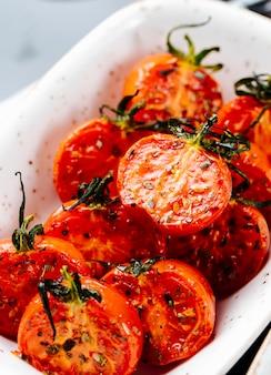 Vista lateral próxima tomates secos ao sol em um prato