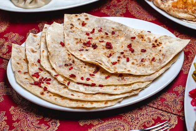 Vista lateral qutab com carne moída e bérberis secas em um prato