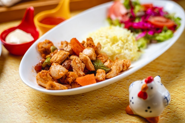 Vista lateral ragout de frango peito de frango grelhado com cebola cenoura pimentão salada de legumes e guarnição de arroz em um prato