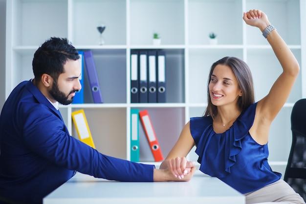 Vista lateral, retrato, de, homem mulher, armwrestling, exercendo pressão, ligado, um ao outro