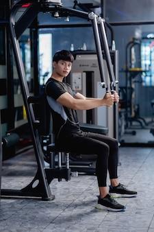 Vista lateral, retrato jovem bonito em roupas esportivas, sentado para fazer exercícios de pressão no peito da máquina no ginásio moderno.