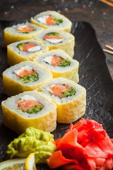 Vista lateral rolo conjunto com gengibre em conserva e wasabi no prato escuro