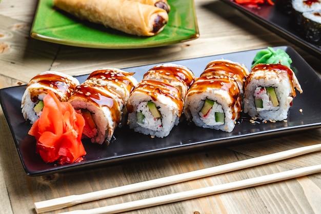 Vista lateral rolo de filadélfia com carne de caranguejo cong enguia pepino abacate molho teriyaki gengibre e wasabi em uma bandeja