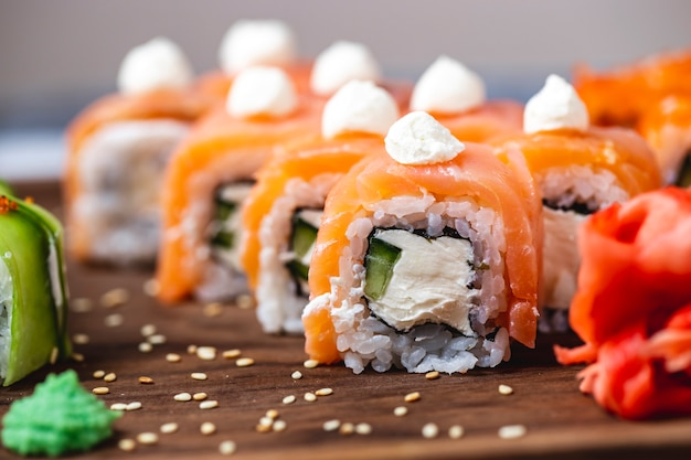 Vista lateral rolo de filadélfia com creme de queijo cucumper salmão wasabi gengibre e gergelim sementes em uma placa
