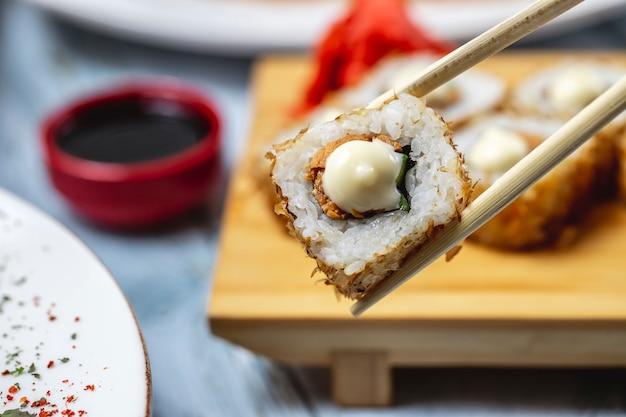 Vista lateral rolo de pele de salmão com pepino maionese e molho de soja em cima da mesa