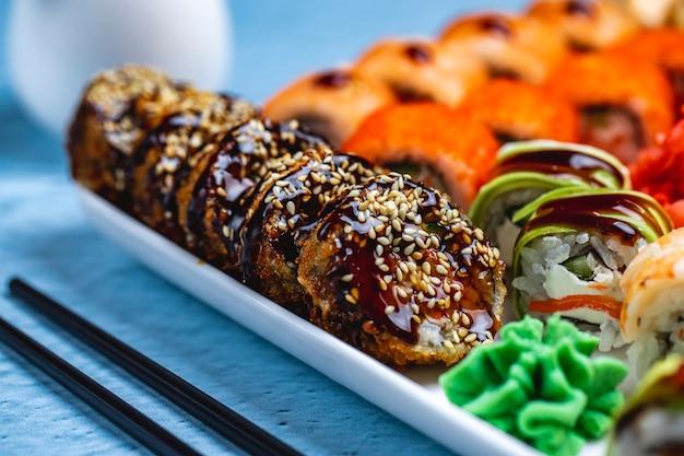 Vista lateral rolo quente rolo de sushi frito com molho de teriyaki sementes de gergelim e gengibre em um prato