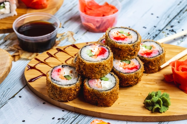 Vista lateral rolo quente rolo de sushi frito com tomate salmão pepino queijo creme de gengibre wasabi e molho de soja em cima da mesa