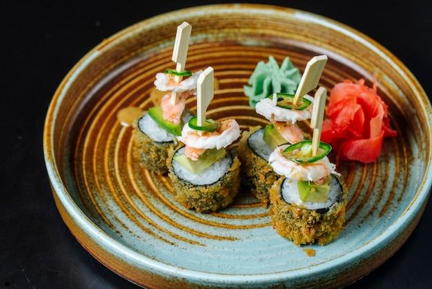 Vista lateral rolos de sushi frito com camarão com wasabi e gengibre em um prato